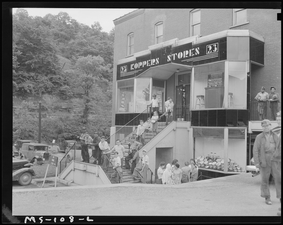 Image shows miners and their families in West Virginia standing outside of the Kopper Stores, a company store for miners.