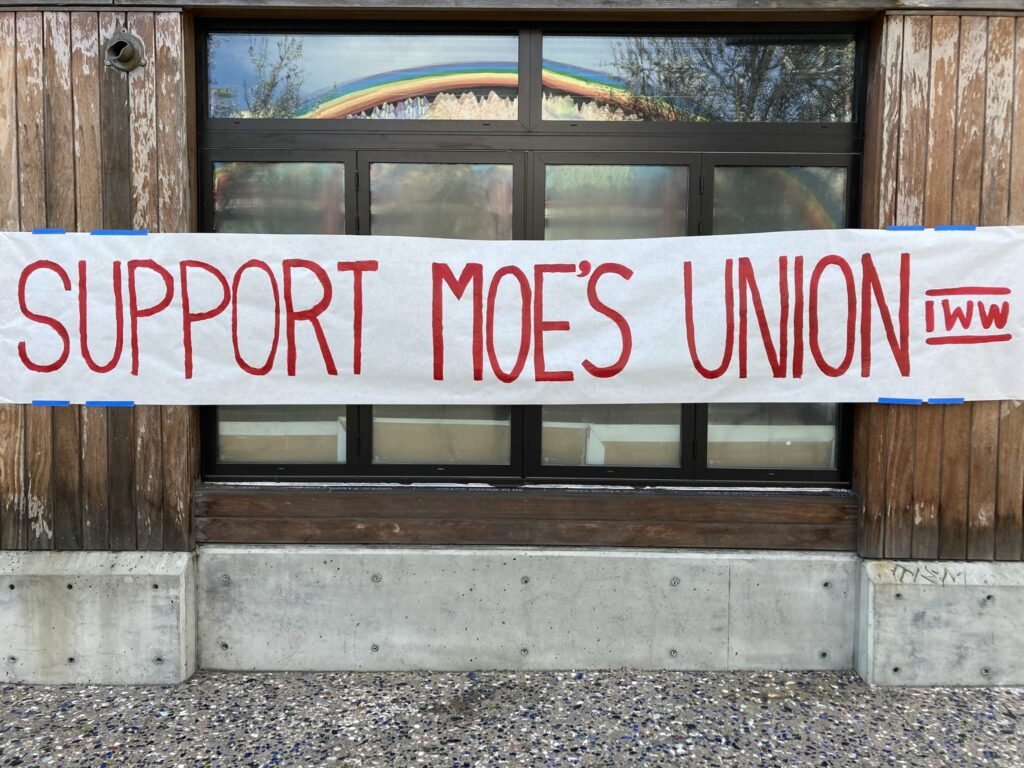 """Photo shows image of banner with handwritten text that reads """"Support Moe's Union"""" and """"IWW"""""""